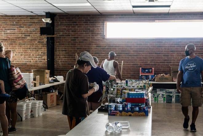 Chauvin residents and volunteers gather Friday at the Ward 7 Citizens Club in Chauvin, which has been turned in to a distribution center for food and supplies in the wake of Hurricane Ida.