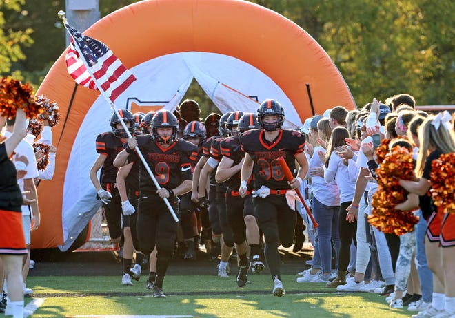 Tecumseh's Jayden Amaya (9) and Keedyn Riedel (36) lead the team out of the tunnel prior to Friday's game against Pinckney.