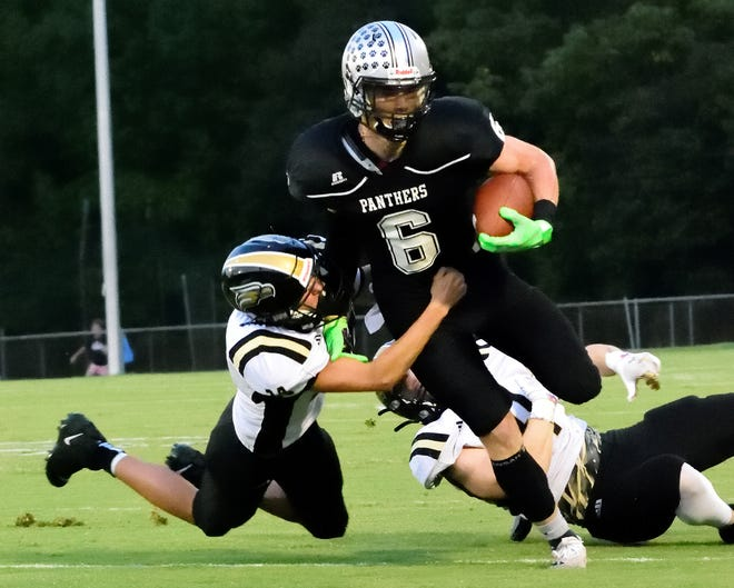 Ledford's Owen Finley gains some yards before being taken down by East Davidson's Camron Cabe Friday night at Ledford. [David Yemm for The Dispatch]
