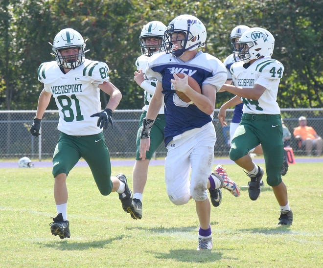 West Canada Valley Indian John Michael runs with the ball and a trio of Weedsport Warriors in pursuit during Saturday's season-opening eight-player football game.