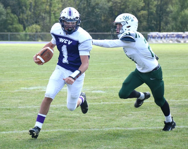 West Canada Valley quarterback Brayden Shepardson (1) runs with the ball while Weedsport defender Quinn Rudick tries to grab him from behind Saturday, Sept. 11, 2021, in Newport, New York.