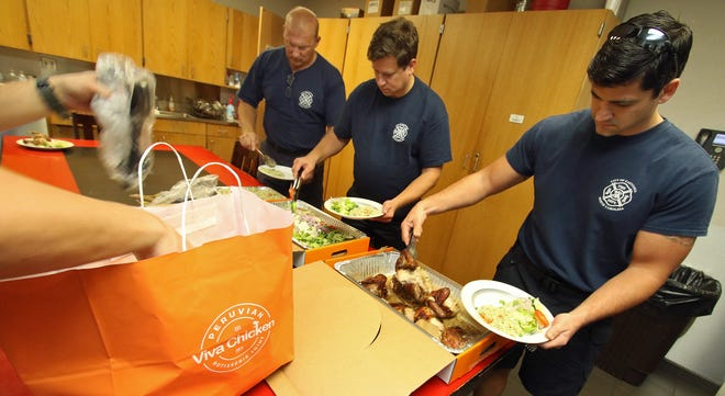 Firefighter Patrick Barlow, right, with his fellow firefighters enjoy a free lunch provided by Viva Chicken Saturday, Sept. 11, 2021, at Gastonia Fire Department Station 4 on Armstrong Park Road.