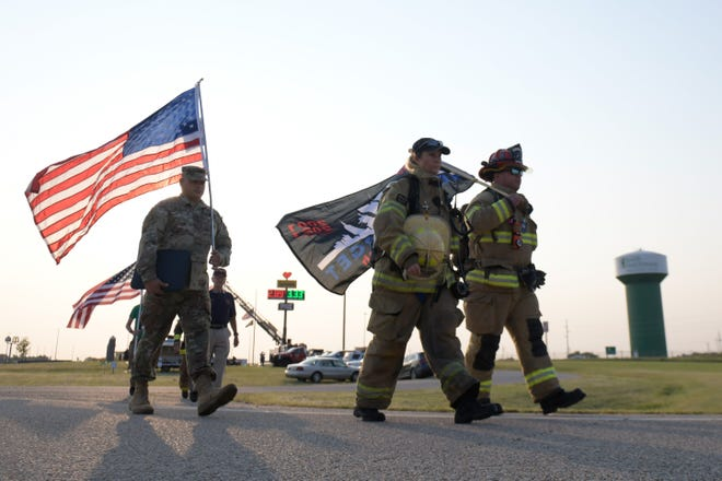 South Hutchinson Fire Department fire chief Shay Barajas-Brooks and Captain Jake Fletchall, right,  begin to walk the 4.2 mile route to commemorate the fallen 343 firefighters on Sept. 11 in South Hutchinson.