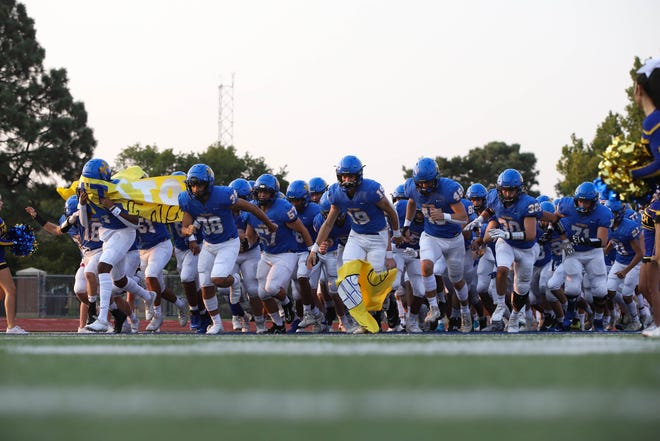 The Hutchinson Salthawks run onto the field prior to kickoff Friday night at Gowans Stadium in Hutchinson. The Buffaloes beat the Salthawks 13-7 in overtime.