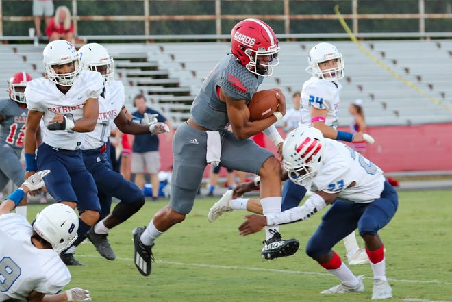 Jacksonville quarterback Josh Benton tries to break a tackle in the Cardinals' 48-7 win over West Carteret on Friday.
