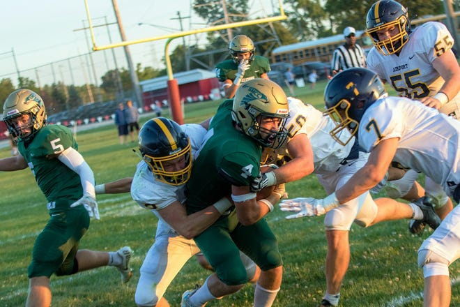 SMCC's Nico Bellino (4) is tackled by Airport's Nik Hammond (2), Brayden Moore (50) and Jack Mills (7) Friday. The Falcons won without head coach Adam Kipf.