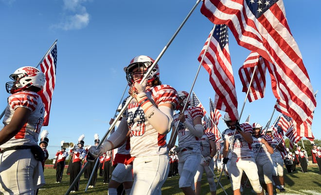 Monroe High School varsity football player Noah Miller and the team carried between 30 to 50 American Flags provide by the AIMS program onto the field Friday.