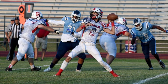 Quarterback Caleb Winkleman prepares to throw a touchdown pass during a 57-14 win over Ann Arbor Skyline Friday night.