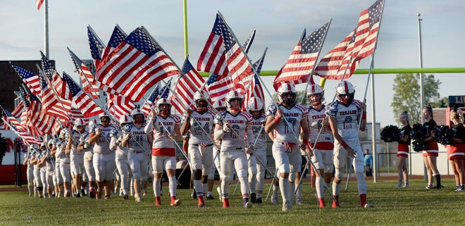 The Monroe High School varsity football team carries dozens of American Flags provide by the AIMS program on Friday. To show their patriotism, the Monroe Football Mothers Club sponsored the First Responders Night as student wore Red, White and Blue clothing, painted their faces and the players wore new jerseys.