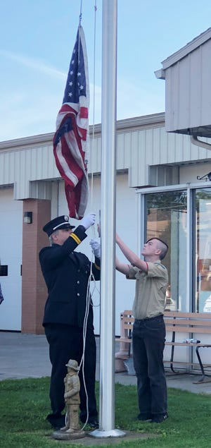 Daniel McWilliams and his son, Daniel McWilliams II, raise the American flag during a 9/11 memorial ceremony Saturday at the Shortsville Fire Department.