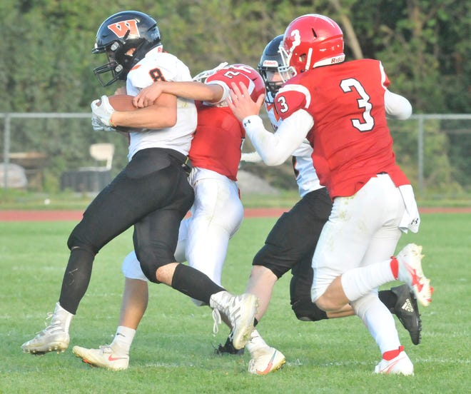 Red Jacket's James Sibeto (2) hauls down Jeremiah Havens (8) of Wellsville as Kyle Damore arrives to help during Friday's game.