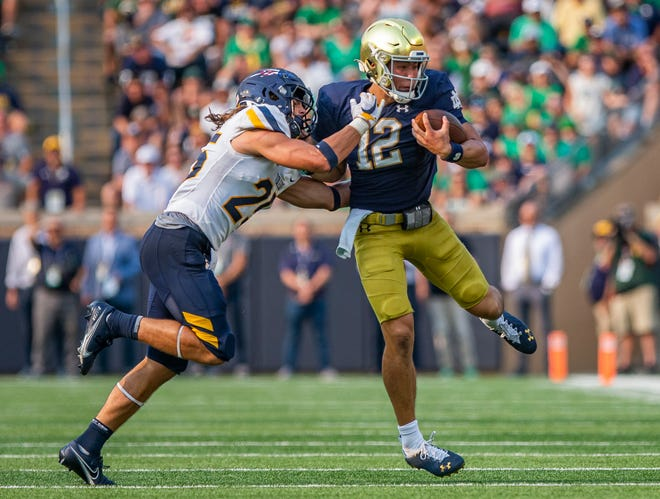 Notre Dame's Tyler Buchner (12) gets pulled down by Toledo's Maxen Hook (25) during Notre Dame's 32-29 win over Toledo in an NCAA football game Saturday, Sept. 11, 2021 at Notre Dame Stadium in South Bend.