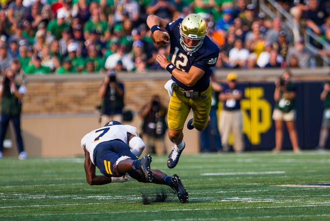 Notre Dame QB Tyler Buchner (12) dives around Toledo's Zachary Ford (7) during the Notre Dame's 32-29 win over Toledo, Saturday, Sept. 11, 2021, at Notre Dame Stadium.