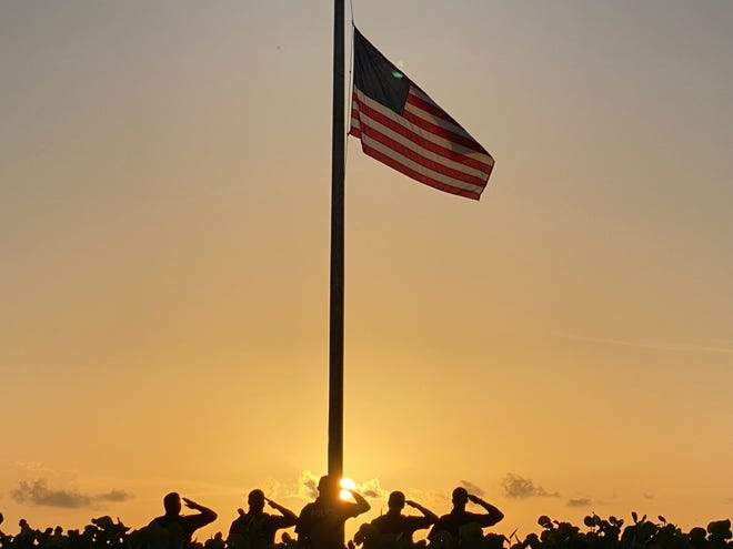 Palm Beach police officers salute as the flag is lowered to half-staff at sunrise Saturday, Sept. 11, 2021, at Midtown Beach. The flags remained lowered at all town facilities until sunset Saturday.