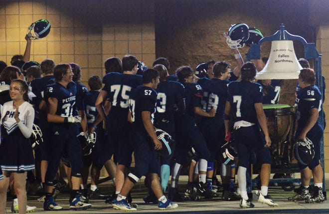 Petoskey players rush to ring the victory bell following a 35-14 win over Alpena, which brought the Northmen a 3-0 start to the season.