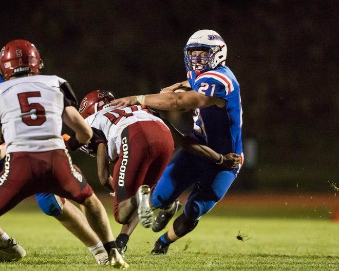 Winnacunnet's Chris Capezzuto breaks free from Concord's Moses Harris during Friday's Division I football game. Capezzuto ran for 69 yards and two touchdowns as Winnacunnet won 42-7.