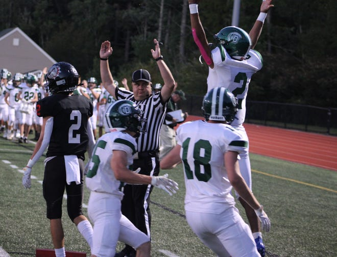 Dover quarterback Darian Sullivan-Lopez jumps in celebration following his 7-yard touchdown run in the first quarter of Friday's Division I football game at Bedford. Sullivan-Lopez rushed for 82 yards and three touchdowns.