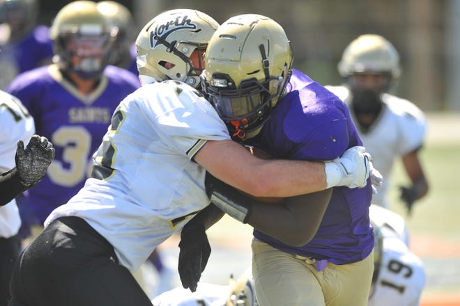 St. Raphael's Moses Meus tries to run through a tackle by a North Kingstown player during a game last weekend.