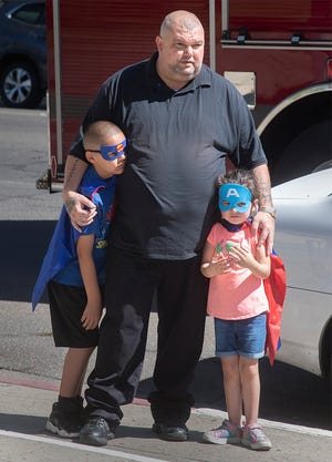"""Ronald Hill and his stepson Isaiah Ortiz and daughter Jordynn Hiil watch the 9/11 20th anniversary observance at the Stockton Civic Memorial Auditorium in downtown Stockton.   """"I brought my kids so they won't forget,"""" said Hill. """"They weren't around (when 9/11 happened), but I want them to know what this day is about."""""""