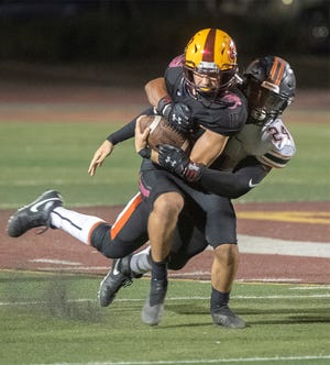 Edison's Aidan Carr, left, is tackled by Central's Amarian Hunter during a varsity football game at Edison's Magnasco Stadium in Stockton.