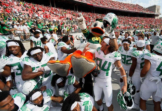 Oregon players carry the Duck mascot off the field following their 35-28 win over the Ohio State Buckeyes at Ohio Stadium in Columbus Saturday.