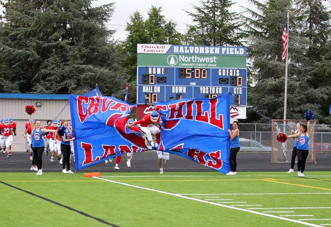 Churchill players break through a banner before Friday's home game with Marshfield
