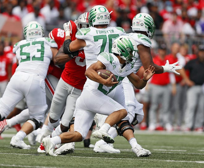 Oregon running back Travis Dye hits a hole opened by Oregon guard Ryan Walk (53) and center Alex Forsyth during the second quarter of Saturday's game.