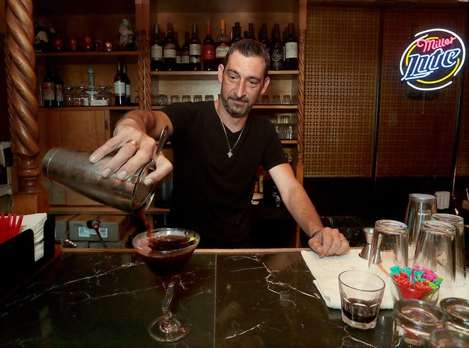 Nick Margaritakis pours the Sparta Steak House signature blueberry martini. Margaritakis, who operates Sparta Steak House and Lounge in Canton, said business has returned to around normal following difficult times during the earlier stages of the pandemic.