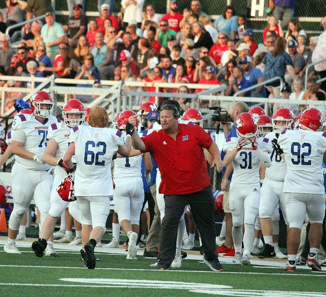 A Martinsville player is greeted by a coach after making a defensive stop during the game against Decatur Central on Friday, Sept. 10, 2021.