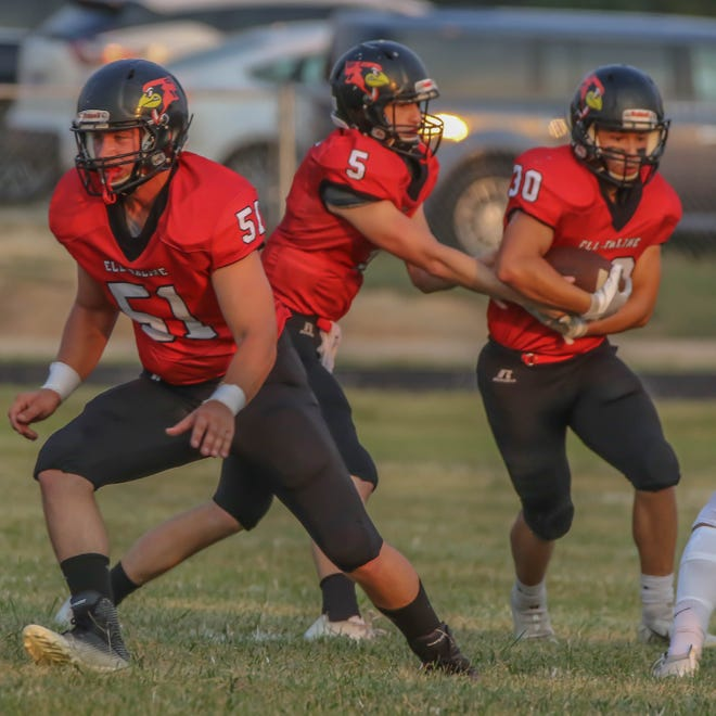 Ell-Saline's Kade Wilson (5) hands off the football to Obed Ruiz (30) while Kayden Goddard (51) blocks during Friday's game against Sacred Heart in Brookville.