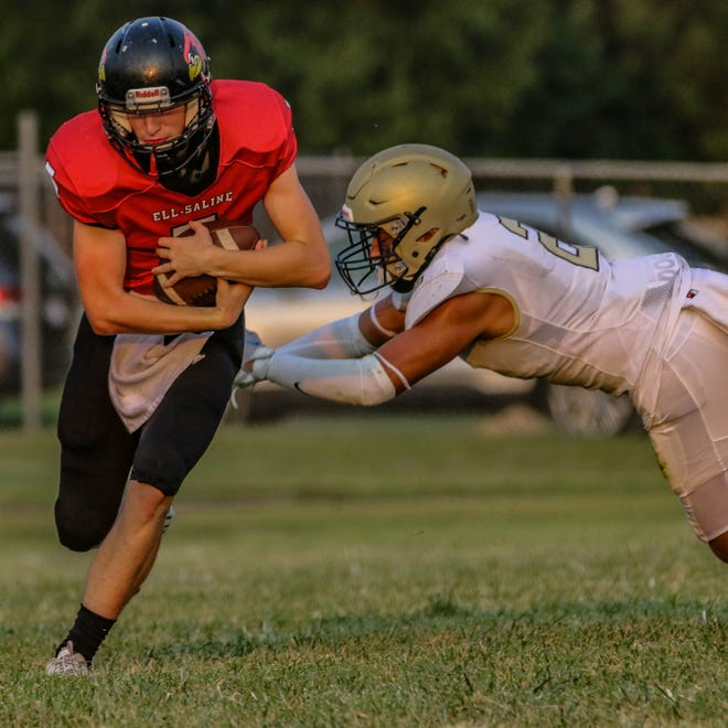 Ell-Saline's Kade Wilson (5) gets past Sacred Heart's Izeyiah Rodriguez (2) during Friday's game in Brookville.