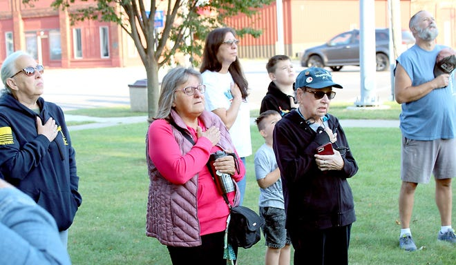 """Marlene Hagerman of Centreville and other attendees at a Sept. 11 memorial event stand at attention for """"The Star-Spangled Banner."""""""