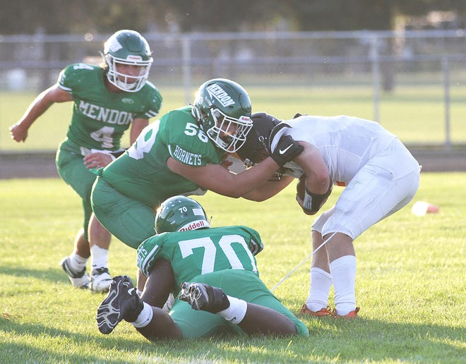Mendon's Khayvien Brown (70) and Noah Iobe (58) combine to record a tackle in the open field for the Hornets on Friday night.