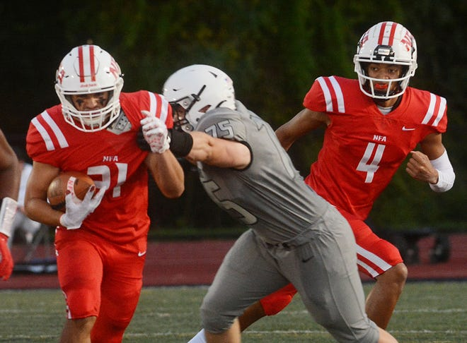 NFA's Jake Kenney (21) gets by Xavier's Alec Pawlowicz for a gain after getting a hand off from quarterback Jayden Desilus (4), right, during the Wildcats' 31-19 loss Friday night in Middletown.