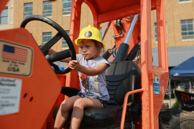 """A child, 3, pretends to steer a piece of machinery on display at Topeka's eighth """"Touch-A-Truck"""" event, which was held at Evergy Plaza this year for the first time."""