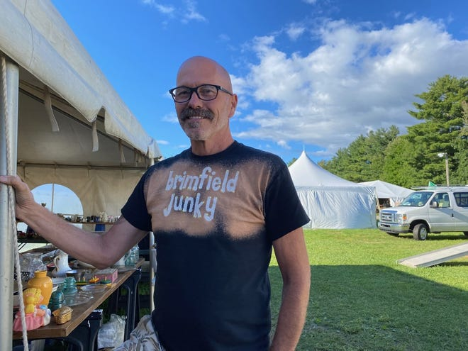 """Wearing his blinged-out """"Brimfield Junky"""" T-shirt, Ross Allard of Chicopee says he sells his wares at the Brimfield Outdoor Antiques Shows starting at $5 per item on the first day, and ending with $1 per item Sunday, the shows' final day."""