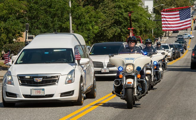 """The funeral procession for Worcester Police Officer Ignacio J. """"Iggy"""" Garcia travels under a large flag on Lincoln Street in Worcester on Saturday."""