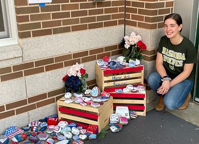 Madison Oxnard, a freshman at Nashoba Regional High School, shows off the rocks Nashoba students painted to remember those who died on Sept. 11, 2001. Madison is a member of Project 351 and the project, which featured rocks with names of people who died in the terrorist attacks, was her idea. She also organized a moment of silence Friday, Sept. 10, for students to participate in the commemoration.