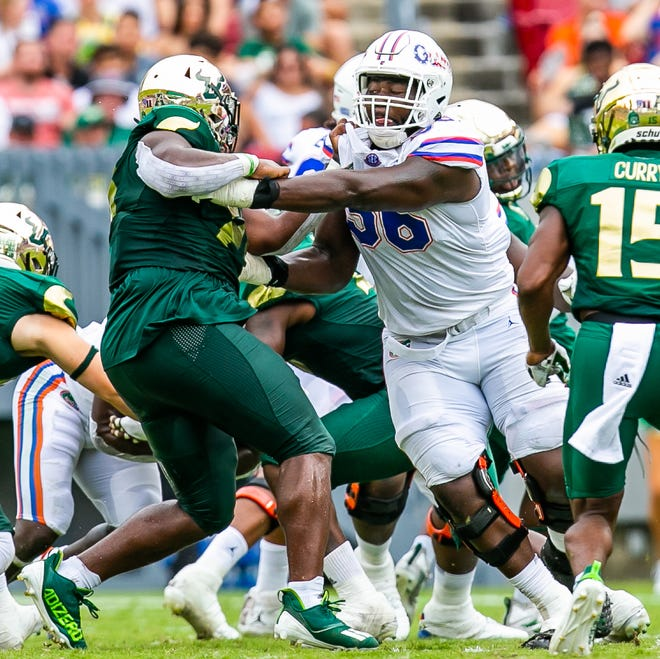 Florida offensive lineman Jean Delance (56) drives a South Florida defensive tackle away from his quarterback in the first half Saturday at Raymond James Stadium in Tampa.