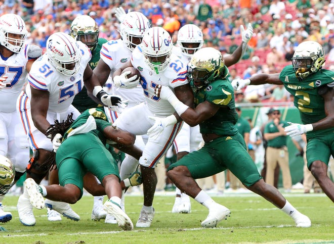 Florida running back Dameon Pierce (27) pushes through USF defenders to score the game's first touchdown Saturday at Raymond James Stadium in Tampa.