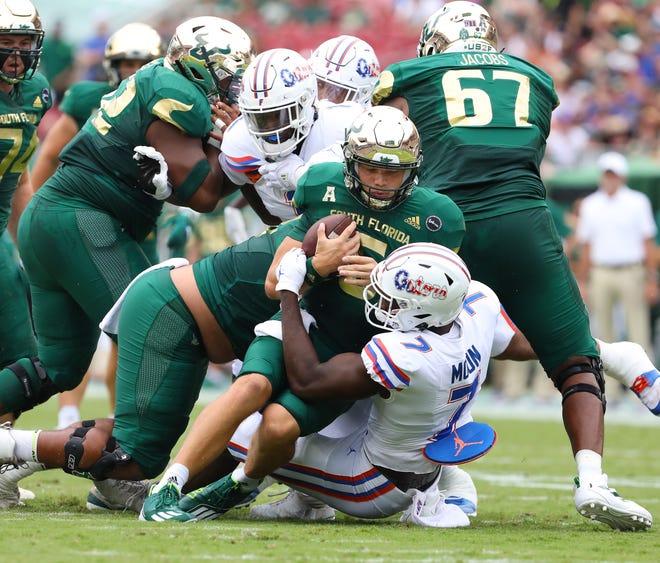 Florida linebacker Jeremiah Moon (7) sacks South Florida quarterback Cade Fortin (6) on Saturday at Raymond James Stadium in Tampa.