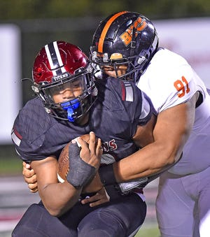 Gadsden City's C.J. Miller tries to break free from Hoover's Chaleb Powell during Friday's game.