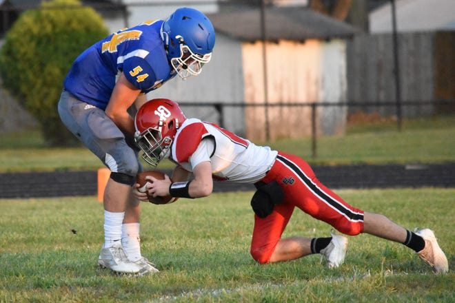 Mitchell's Trey Craig drags down Eastern Greene quarterback Jonas Hawk for a sack.