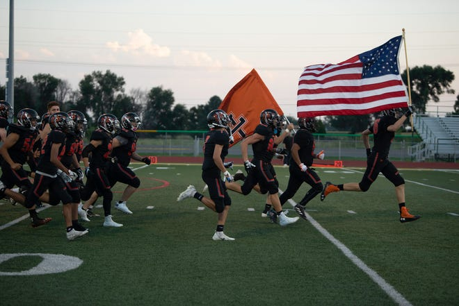 The La Junta High School football team takes the field at Pueblo County Hornet Stadium ahead of a matchup with Alamosa on Sept. 10. The Tigers will play their first game on their home field Oct. 8, after new turf recently was installed at Tiger Stadium.