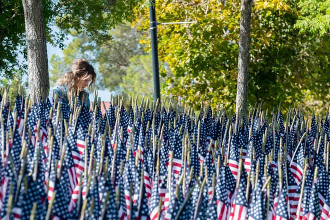 An attendee takes a photograph of memorial flags on a hillside at Victor Valley College on Saturday, Sept. 11, 2001.