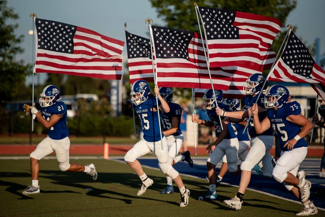 Harper Creek varsity football players honor the 13 U.S. troops killed in Afghanistan last month on Friday, Sept. 10, 2021 at Harper Creek High School.