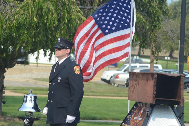 Battle Creek Firefighter Jake Gray rings the last alarm during the 9/11 ceremony Saturday. Gray stands in front of a piece of beam from the World Trade Center.