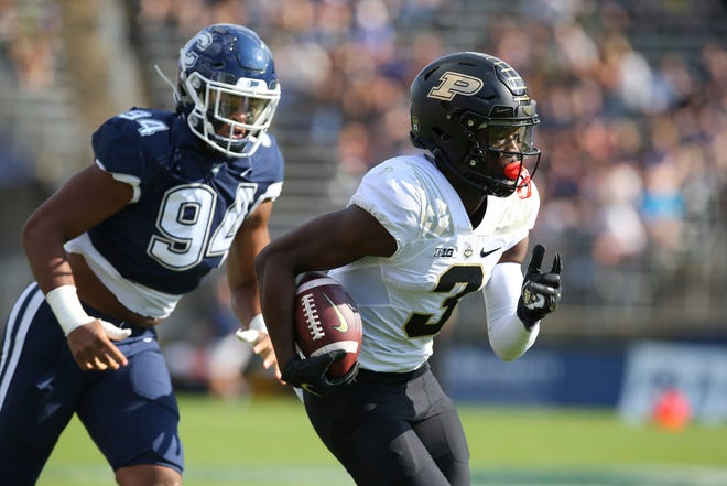 Purdue wide receiver David Bell (3) is pursued by Connecticut defensive lineman Nick Harris (94) during the first half of an NCAA football game on Saturday, Sept. 11, 2021, in East Hartford, Conn.