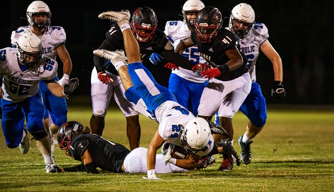 Lexington Catholic running back Walker Hall (24) was upended after a short gain during second-half action Friday night at Pleasure Ridge Park. The Knights defeated the Panthers 45-30. Sept. 10, 2021