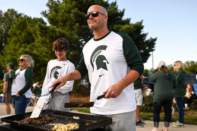 Jason Williams cooks breakfast on a flattop griddle while tailgating near the Breslin Center before Michigan State's football game against Youngstown State on Saturday, Sept. 11, 2021, in East Lansing.